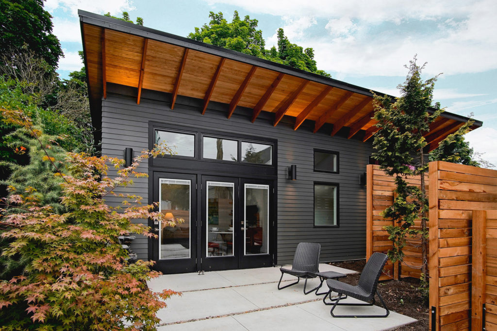 Dark gray house with orange overhang and large spacious doors